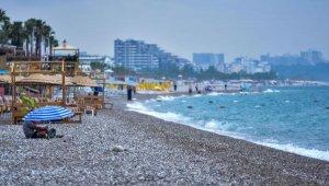 Antalya'da aniden bastıran yağmur, sahildekilere zor anlar yaşattı